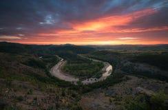 在河弯的火热的日落在山 免版税库存图片