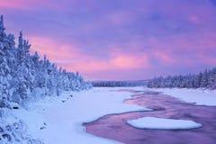 在河急流在一个冬天,芬兰拉普兰的日出 免版税图库摄影