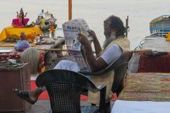 在河恒河的边界的印度教士读书报纸 免版税库存照片