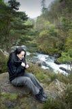 在河感觉寒冷附近的女性远足者 库存照片