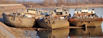 在河放弃的三艘老生锈的被放弃的驳船 库存图片