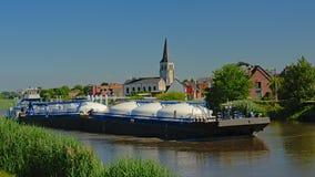 在河斯海尔德河的货轮有高耸的在佛兰芒乡下 免版税库存照片
