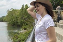 在河旁边的坚强的妇女有帽子的 库存图片