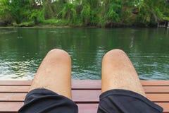 在河旁边的腿人在假日 免版税库存图片