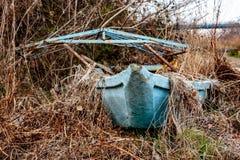 在河旁边的被放弃的蓝色小船 库存图片