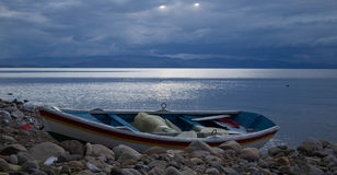 在河沿的土气渔船在日落 免版税库存图片