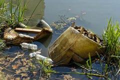 在河沿的塑料污染 免版税库存照片
