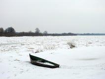 在河海岸在冬天,立陶宛的老木小船 库存照片