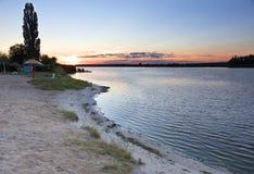 在河海滩、夏天明亮的日落和太阳` s光芒的反射在河的镇静水的 免版税库存图片