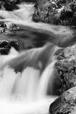 在河溪的岩石在流动在长的曝光的缎软的瀑布 库存照片