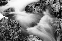 在河溪的岩石在流动在长的曝光的缎软的瀑布 免版税库存照片