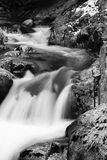 在河溪的岩石在流动在长的曝光的缎软的瀑布 库存图片