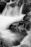 在河溪的岩石在流动在长的曝光的缎软的瀑布 免版税图库摄影