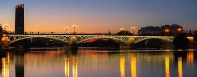 在河瓜达尔基维尔河日落的,塞维利亚,安达卢西亚,西班牙的特里亚纳桥梁 免版税库存图片