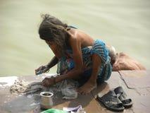 在河甘加的河岸的瓦腊纳西,北方邦,印度- 2009 11月2日,老妇人洗涤的衣裳 免版税库存图片