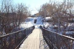 在河的Ñ  Ñ€ÑƒÑ  Ñ 摇晃的老停止步行桥在冬天段落的村庄对另一边 库存图片
