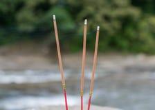 在河的三根佛教灼烧的香火棍子 免版税库存照片