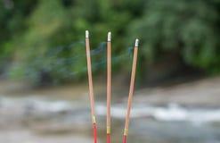 在河的三根佛教灼烧的香火棍子 库存照片
