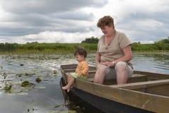 在河的夏天小船的坐有一个小女孩的一名妇女。 库存图片