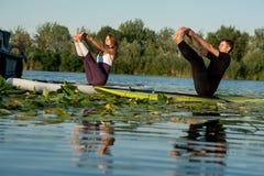 在河的夫妇实践的瑜伽 免版税库存照片