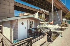 在河的居住船有sailsboat的在都市城市具体桥梁下  库存图片