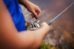 在河的年轻人渔 拿着标尺的fiserman特写镜头 作为设备捕鱼伙计智慧 空转 免版税库存图片