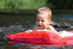在河的愉快的新男孩航行 免版税库存图片