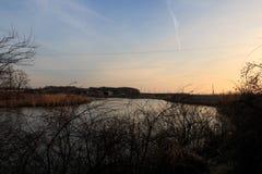 在河的日落在村庄 库存照片