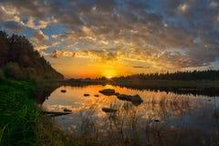 在河的日落太阳有天空的,与美丽的云彩和惊人的反射在水中 免版税库存照片