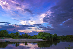在河的晚上在春天,与紫罗兰色的云彩的天空 免版税库存照片