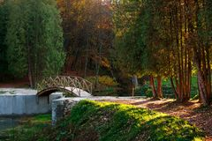 在河的木桥有五颜六色的树的在秋天公园 图库摄影