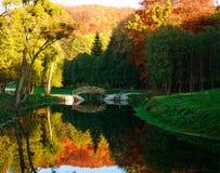 在河的木桥有五颜六色的树的在秋天公园 免版税图库摄影