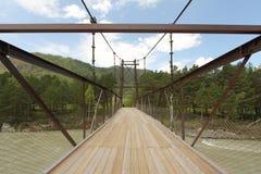 在河的木桥蓝天背景的  免版税库存照片