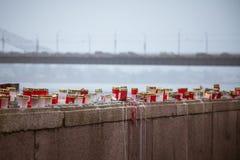 在河的栏杆的一个美好的红色和白色蜡烛支持 免版税库存图片