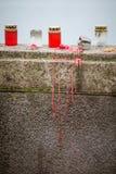 在河的栏杆的一个美好的红色和白色蜡烛支持 免版税图库摄影