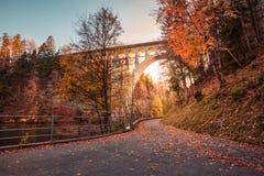 在河的桥梁与秋天叶子的日落的 库存图片