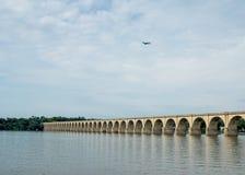 在河的桥梁和在天空的一架喷气机 免版税图库摄影