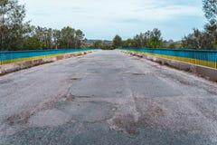 在河的桥梁有被毁坏的柏油路的在乌克兰 免版税图库摄影