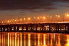在河的桥梁,光在一条冻河在晚上, Dnieper市的冰反射了 免版税库存照片