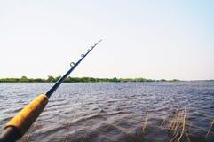 在河的水域中投掷的钓鱼竿 免版税图库摄影