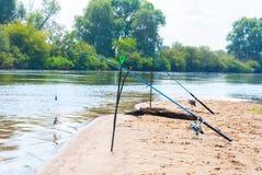 在河的河岸的钓鱼竿蓝天背景的  库存图片