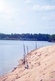 在河的河岸的钓鱼竿蓝天背景的  图库摄影