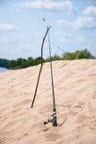 在河的河岸的钓鱼竿蓝天背景的  免版税库存图片