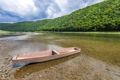 在河的清楚的水的老小船有森林的盖了小山b 免版税库存照片