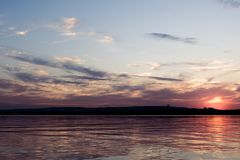 在河的红色紫色日落 图库摄影