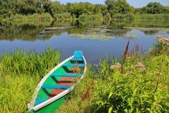 在河的美丽如画的河岸的小船 免版税库存图片