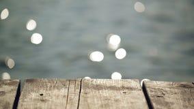 在河的老木码头跳船用闪耀在Bokeh的水作为美好的自然本底 影视素材