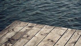 在河的老木码头跳船用闪耀在Bokeh的水作为美好的自然本底 股票视频