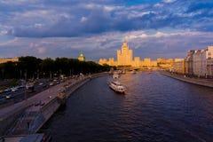 在河的船风帆日落光的 一种都市风景和一栋居民住房与一个尖顶在背景 免版税库存照片