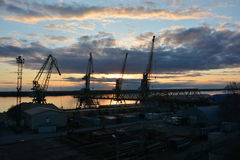 在河的起重机在很多日落的口岸的 免版税库存图片
